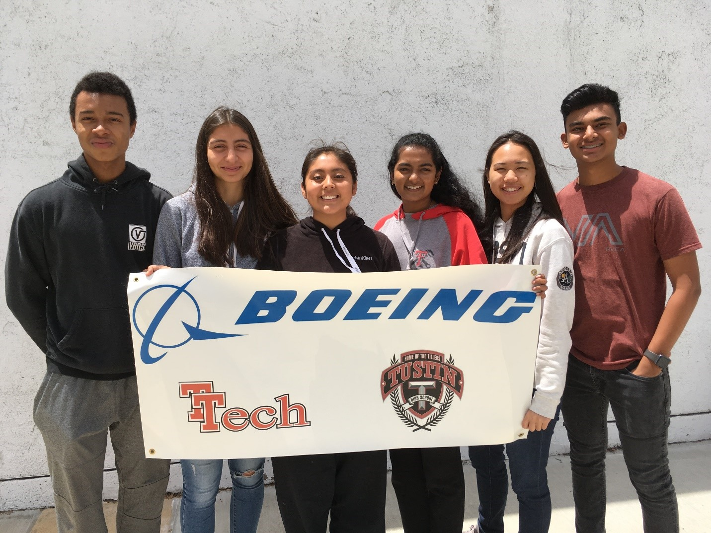 Six TUSD students holding a Boeing T-Tech Banner
